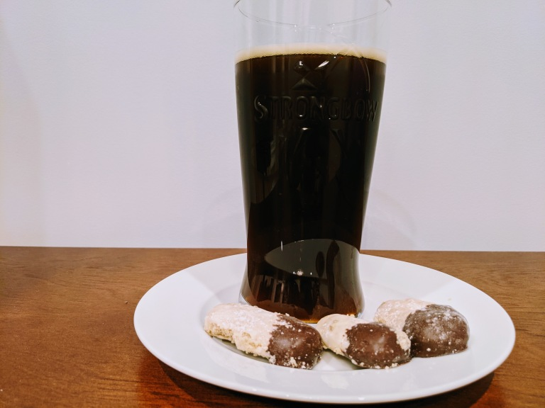 A glass of beer with cookies